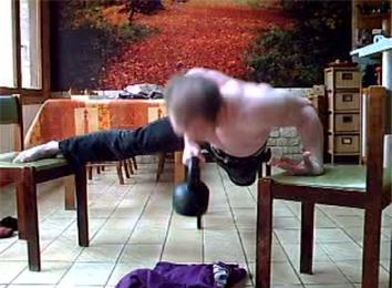 Most Consecutive One-Armed Back-Of-Hand Push-Ups On Three Chairs While Carrying A 20-Kilogram Kettlebell
