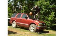 Most Basketball Dribbles In One Minute While Standing On The Hood Of An SUV