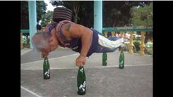 Most Consecutive Push-Ups Performed On Four Soda Bottles With 50-Pound Weight On Back